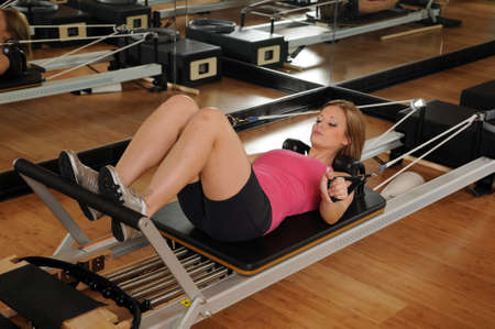 machine: Young woman working out on a Pilates machine Stock Photo