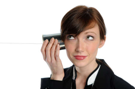 Beautiful businesswoman listening to tin can phone with string photo