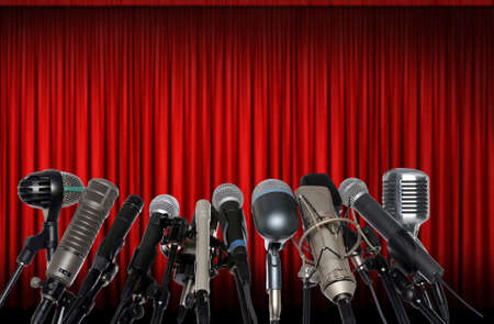 press conference: Microphones in front of red curtain Stock Photo