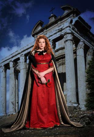Jonge vrouw gekleed in Renaissance kleding met ruïnes op achtergrond