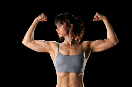 Mature woman flexing muscles isolated over black background Foto de archivo