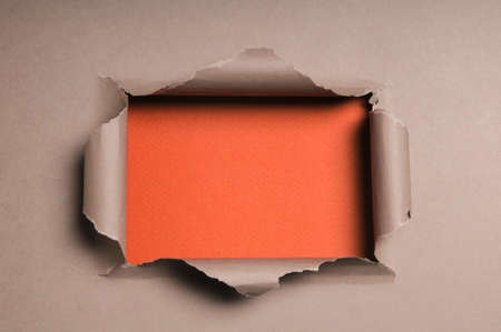 folds: Beige paper ripped to form a rectangle over orange paper in background Stock Photo