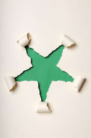 discolored: Old discolored paper ripped to form star over green background