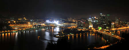 City of Pittsburgh at night with stadium lights on photo