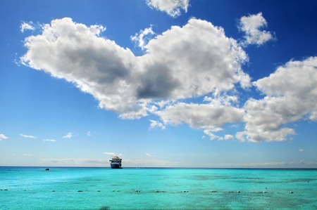 Cruise ship anchored in colorful Caribbean waters with clouds above photo