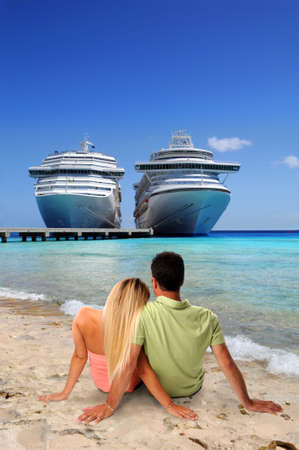 a big ship: Man and Woman relaxing on beach with cruise ships in background