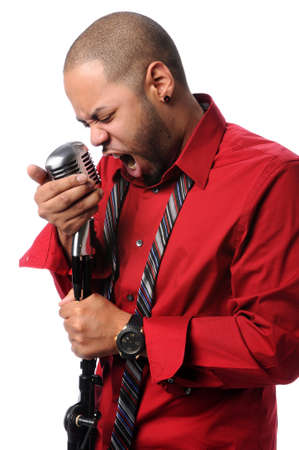 Young African American man singing into vintage microphone photo