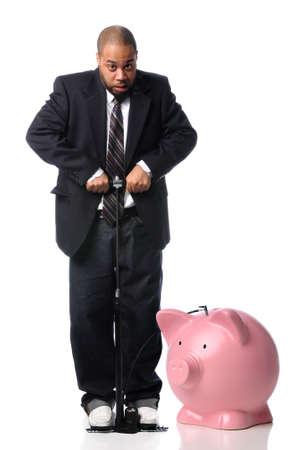 African American businessman inflating piggy bank over white background photo