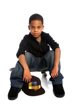 Young African American boy sitting on skateboard isolated over white photo