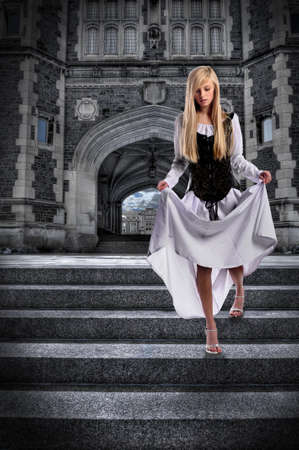 Beautiful young woman descending steps of castle