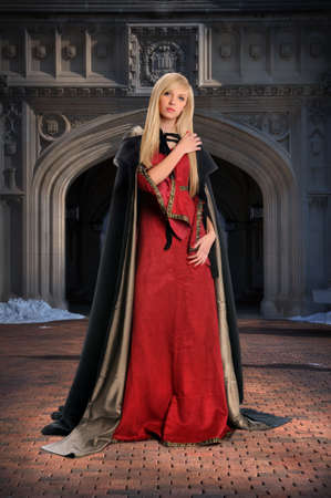 cloak: Beautiful Renaissance woman standing in front of castle Stock Photo