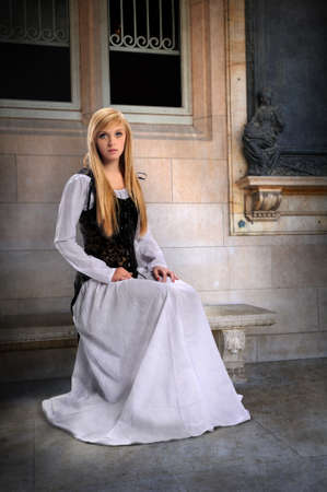 Beautiful young Woman dressed in Renaissance clothing sitting on bench photo