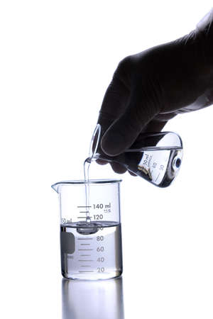 Lab technician wearing latex glove using poring liquid into flask Stock Photo - 8025274