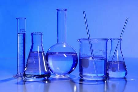 Laboratory glassware in blue light over reflective table photo