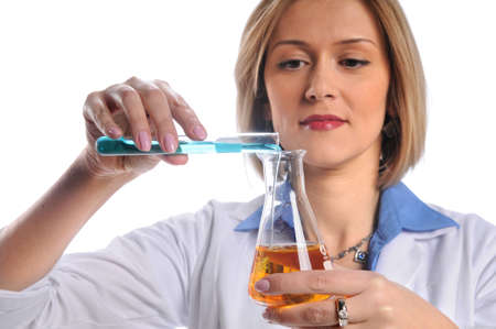 Female lab tech mixing liquids from test tube and flask Stock Photo - 8025276