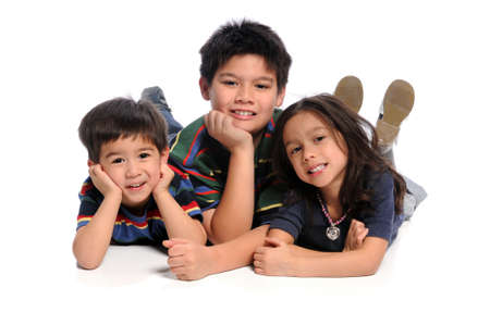 multiracial children: Children laying on the floor isolated over white background