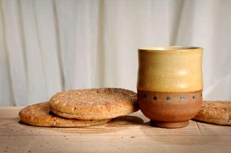 santa cena: Pan y una taza de vino, s�mbolos de la comuni�n en la mesa de madera