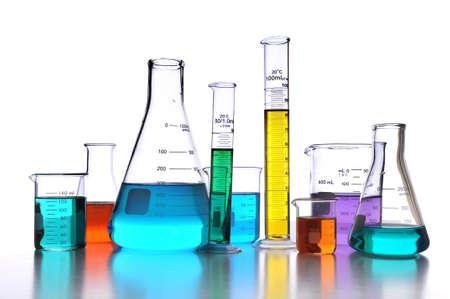 Cristalería de laboratorio sobre fondo blanco con reflexiones sobre la superficie