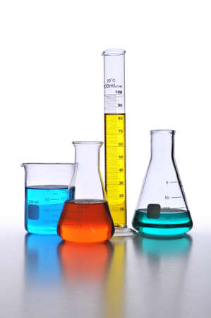 Laboratory glassware with color liquids over white with surface reflections Stock Photo - 8025253