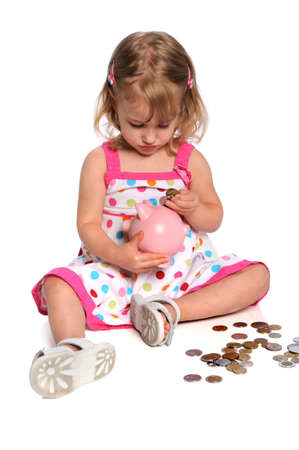 inserting: Young girl inserting coins into piggy bank