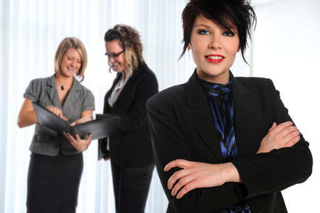 Portrait of young businesswoman with arms crossed with coworkers in background Stock Photo - 8110516