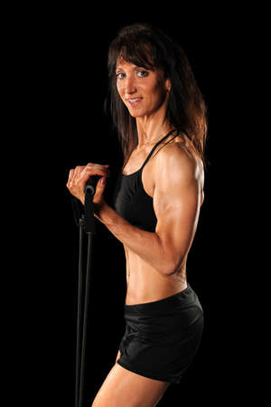 Portrait of woman exercising with elastic band isolated over black background Stock Photo - 8110354