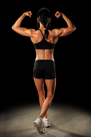 strong: Female athlete flexing arms in view from behind