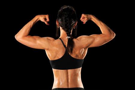 Female athlete showing back isolated over black background Imagens