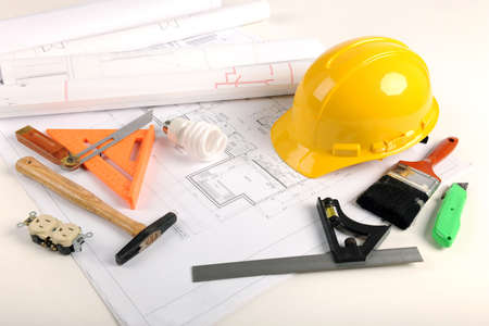 Architectural plans, hardhat and tool over draft table