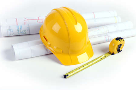 Architectural plans, hardhat and measuring tape over white table photo
