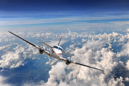 Airplane flying high above the clouds Stock Photo