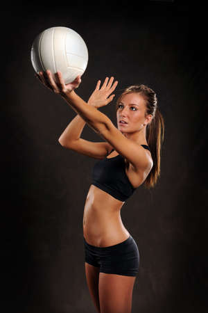 dark: Beautiful young woman playing volleyball over dark background
