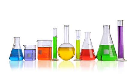 Cristalería de laboratorio con líquidos de diferentes colores aislados sobre fondo blanco
