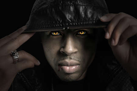 Portrait of African American vampire with hood over head with strong directional light photo