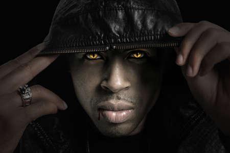 Portret van Afro-Amerikaanse vampire met kap over hoofd met sterke directionele licht