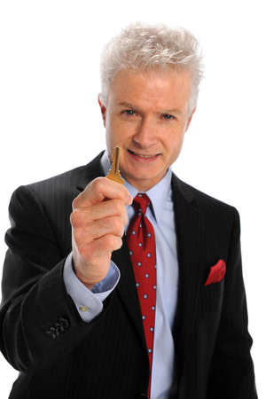 Mature businessman holding key isolated over white background - Selective focus on hand and key photo