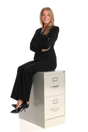 portrait of beautiful businesswoman sitting on file cabinet isolated over white background