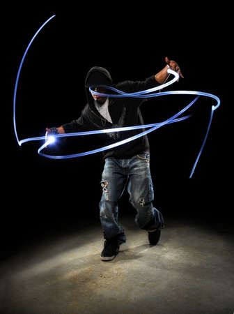 African American hip hop dancer with LED lights painting patterns photo