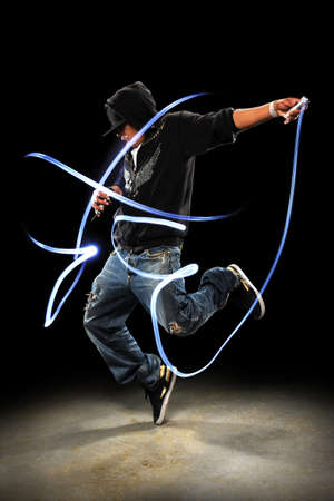 Hip hop dancer performing with LED lights dancing over dark background with spotlight