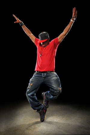 hip hop: African American hip hop dancer performing over dark background with spotlight