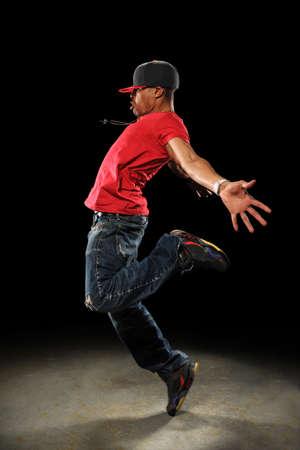 Amerikaans hip hop danser uitvoeren over donkere achtergrond met spotlight