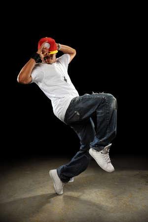 hoodie: African American hip hop dancer performing over dark background