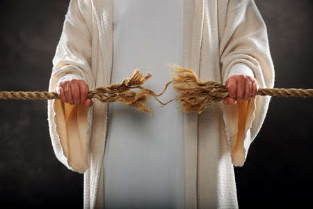 fray: Jesus hands holding frayed rope over dark background Stock Photo