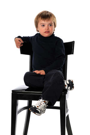 sitting down: Child with Down Syndrome sitting on chair isolated over white background