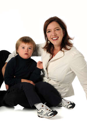 Mother and son with Down syndrome sitting isolated over white background photo