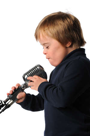 Boy with Down Syndrome singing into vintage microphone isolated over white background photo