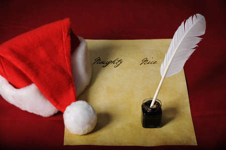 naughty or nice: Santas List with Naughty and Nice columns and quil, ink, and parchment paper Stock Photo