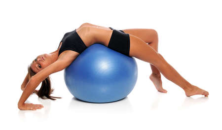 ball stretching: Young woman stretching on fitness ball isolated over white background