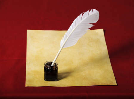 inkwell: Inkwell with quill and old paper over red background
