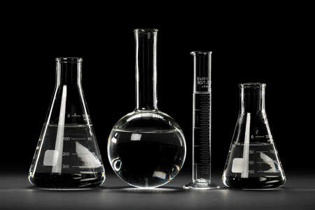 Laboratory glassware over dark background with reflections on table photo